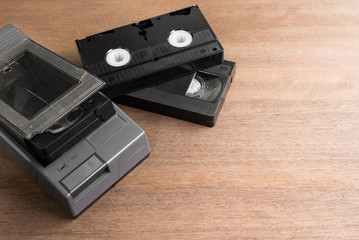 crack vhs rewinder and video cassette tape on wooden board with copy space. old technology concept.