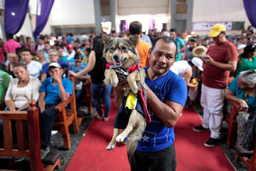 A man carries his dog during a mass in honor of Saint Lazarus in the indigenous community of Monimbo in Masaya