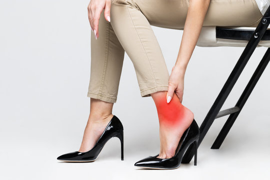 Tired woman touching her ankle, suffering from leg pain because of uncomfortable shoes, feet pain wear high heel shoes/Syndrome of office work concept/Swelling of feet in shoes/Foot fatigue