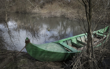 green canoe parked in the shore of Alviela river next to Pombalinho, Santarém, Portugal