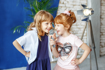 Two funny children sing a song in karaoke. The concept is childhood, lifestyle, music, singing, friendship.