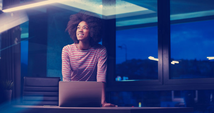 black businesswoman using a laptop in night startup office