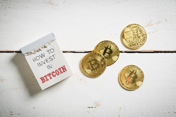 "Bitcoins with tear-off calendar and message ""How to invest in Bitcoin"""