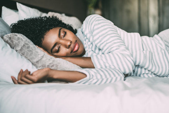 close up of a pretty black woman with curly hair sleeping in bed closed eyes
