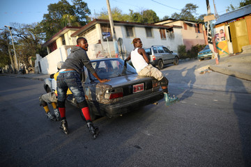 Skaters hold themselves up to a car to move along a street in Port-au-Prince