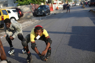 Youths skate down a street in Port-au-Prince