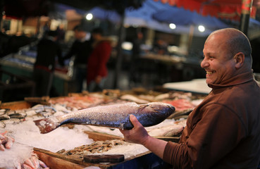 A vendor shows a fish to customers at a fish market near the canal of Port Said