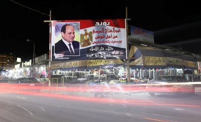 A banner supporting President Abdel Fattah al-Sisi's re-election hangs at a clothes market near the canal of Port Said