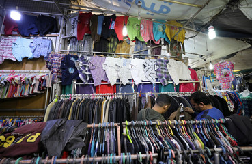 Men look at a jacket in a clothes market  near the canal of Port Said