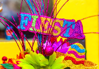 The word 'fiesta' written in colorful glitter letters with sombrero and paper flowers