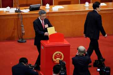 Hu Chunhua casts his ballot next to Chongqing party secretary Chen Miner at the seventh plenary session of the National People's Congress (NPC)