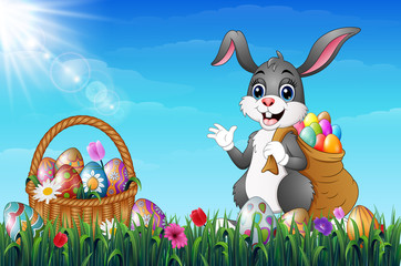 Easter bunny carrying sack full of easter eggs in a grass field