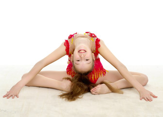 The little gymnast perform an acrobatic element on the floor.