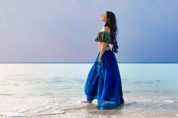 beautiful young stylish woman in blue skirt on the beach