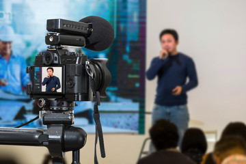 Professional digital Mirrorless camera with microphone on the tripod recording video blog of asian Speaker on the stage seminar, Camera for photographer or Video and Technology Live Streaming concept