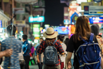 Back side of Young Asian traveling women walking and looking in Khaosan Road walking street in night time at Bangkok, Thailand, traveler and tourist concept