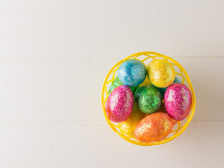 Basket with colorful eggs on a white rustic table. The view from the top.