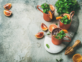 Blood orange Moscow mule alcohol cocktails with fresh mint leaves and ice in copper mugs on board over grey concrete background, copy space