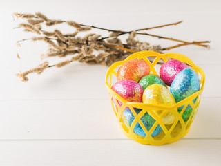 Basket with colorful eggs on a white rustic table.