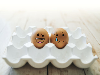 Set of eggs emotion on wood background. Happy and unhappy smileys.