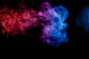 Dense multicolored smoke of blue, red and purple colors on a black isolated background. Background of smoke vape