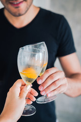 Man's and woman's hands holding wine glasses with orange. Celebration, chill, relax, leisure concept