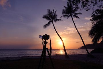 Dslr camera on a tripod while recording pictures of sunrise on the beach