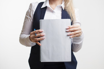 Businesswoman with notepad or organizer shows something. On a white background.