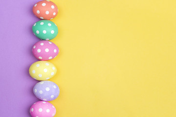 Colored Easter eggs on purple and yellow background.