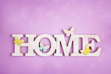Decorative word Home with butterflies on a violet background. Copy space.