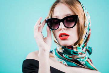 Portrait of a stylish woman posing in sunglasess and scarf on head, isolated on blue background. Horizontal.