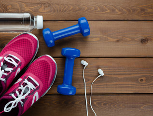 sneakers dumbbells and bottle of water on wooden table background