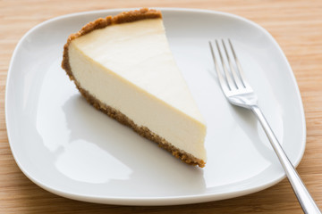 Classic New York cheesecake on white plate. Closeup view, selective focus