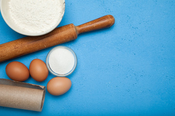 Baking cake in rustic kitchen (eggs, flour, milk, butter, sugar). Background layout with free text space.