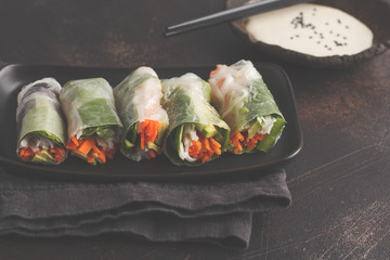Fresh handmade vegan asian spring rolls with rice noodles, avocado, carrots and tahini dressing on black dish, dark background.