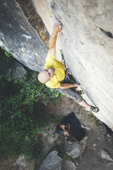 High angle view of climber reaching across for handhold on rock face in limestone wall