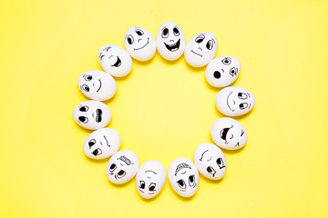 Eggs with drawn cartoon faces with various emotions in circle