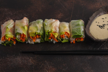 Flat-lay of vegan spring, summer rice paper rolls with vegetables: rice noodles, avocado, carrots and tahini dressing on dark background, copy space.