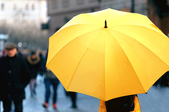 Big yellow umbrella on the city street. Place for text. The view from the top