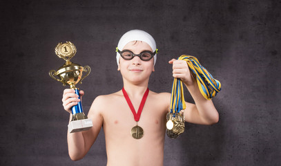 Little boy celebrates his golden trophy in swimming