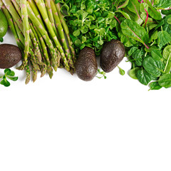 Green herbs, asparagus and black avocado on a white  background. Top view. Flat lay