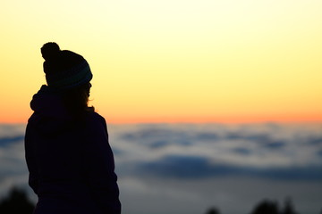 Woman hiker over a sea of clouds in the sunset