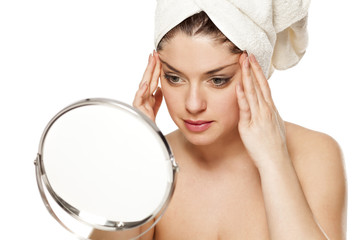 Young beautiful woman with towel on hr head on white background, tightens her face with her hands