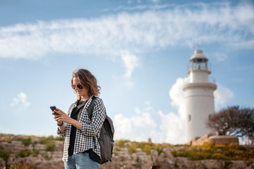Young beautiful woman girl with mobile phone in hands on a background of beautiful scenery, with a lighthouse. Travel to Cyprus