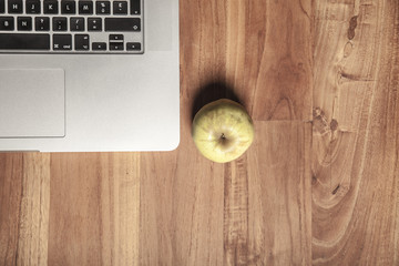 Conceptual photo, an apple on a laptop as a symbol of knowledge and science, copy space next to apple