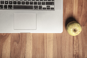 Conceptual photo, an apple on a laptop as a symbol of knowledge and science, top view, copy space