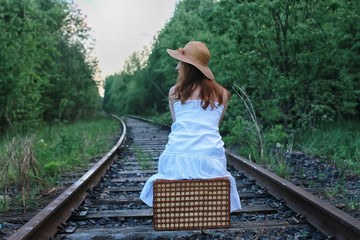 girl in a white sundress and wicker suitcase walking on rails