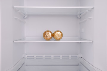 Two metal beer cans inside in empty clean refrigerator