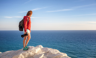 beautiful young woman traveler with a camera stands on a rock and looks at the horizon, freedom, summer travel, profession, freelancer, journalist, blogger, professional photographer