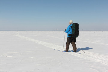 Man in a blue jacket with a backpack is skiing on a snowy river,Ob Reservoir, Russia